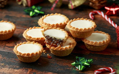 British Christmas iced mince pies with decoration, gifts, green tree branch on wooden rustic table