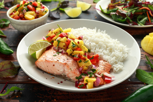 Salmon with mango salsa and white rice on plate