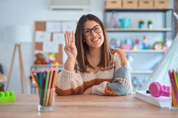 Young beautiful teacher woman wearing sweater and glasses sitting on desk at kindergarten showing...