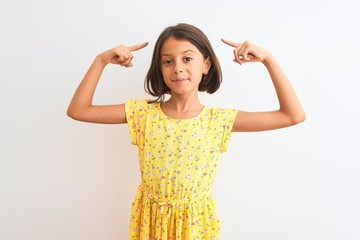 Young beautiful child girl wearing yellow floral dress standing over isolated white background smiling pointing to head with both hands finger, great idea or thought, good memory