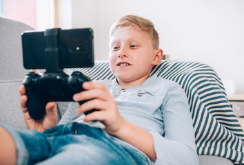 Preteen boy sits at home on cozy sofa, uses gamepad with smartphone. Child use electronic devices concept
