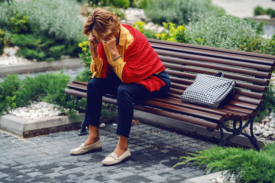 Depressed Caucasian senior woman sitting on bench in park and holding head in hands.