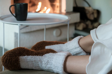 Female legs in knitted socks, covered with a white blanket, on a blurred background a cup with a hot drink and an open fireplace with lighted firewood. Warmth and comfort in a winter evening.