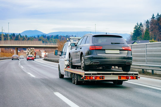 Tow truck with car on warranty in road. Trailer and crash auto delivery. Vehicles hauler on driveway. European transport logistics. Heavy haul trailer with driver on highway.