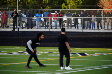 The public watches through a fence as Kaepernick stretches during a special training event at Charles. R. Drew High School in Riverdale