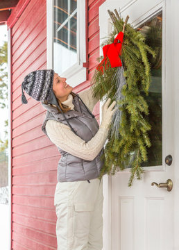 Beautiful, happy, smiling young woman hanging simple, natural evergreen decorations on front door of rustic country style cabin home. People having fun decorating for the holidays.