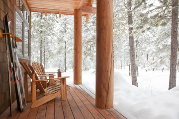 Adirondack chairs and skis on front porch of rustic upscale winter vacation home cabin in snowy forest