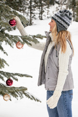Beautiful, happy, smiling, young woman decorating live Christmas tree in snowy winter mountain landscape. People enjoying winter holidays outdoors in nature.