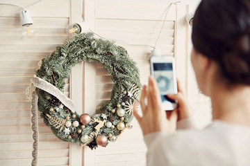 Back view portrait of young woman taking smartphone photo of beautiful Christmas wreath, copy space