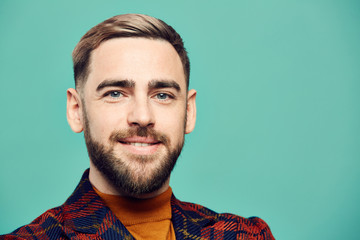 Head and shoulders portrait of bearded adult man smiling at camera while posing against mint green background, copy space