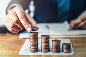 businessman saving money concept. hand holding coin strack. finance and accounting