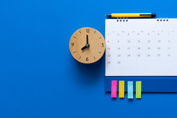 close up of calendar and alarm clock on the blue table background, planning for business meeting or travel planning concept