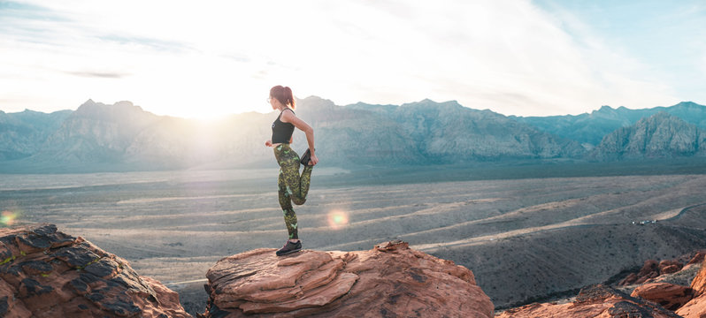 Girl in yoga pants stretching in front of sunset in desert