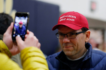 "A man gets his photo taken with his new ""Make Alberta Great Again"" hat while attending a rally for Wexit Alberta, a separatist group seeking federal political party status, in Calgary"