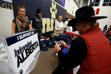 A man in a cowboy hat takes a photo while attending a rally for Wexit Alberta, a separatist group seeking federal political party status, in Calgary