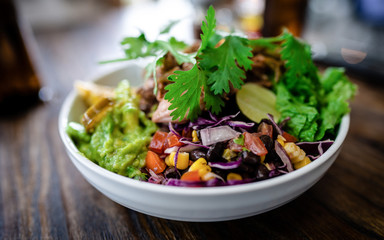 Healthy food concept. Fruit burrito bowl with mixed rice, corn chips, guacamole, grilled corn,...