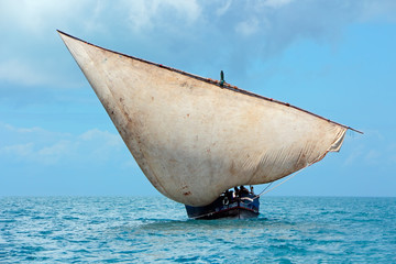 Fotobehang Zanzibar Wooden sailboat (dhow) on the open sea with clouds, Zanzibar.