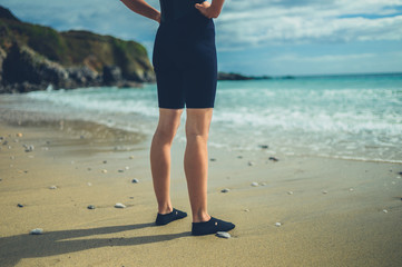The legs and feet of a young woman in wetsuit on the beach