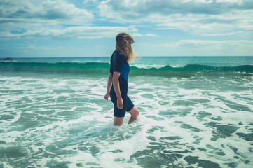 Young woman in wetsuit is standing on the beach with waves crashing in