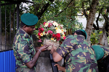 Sri Lanka's Special Task Force members search a flower flower bouquet brought by a supporter of Sri Lanka People's Front party presidential election candidate Gotabaya Rajapaksa in Colombo