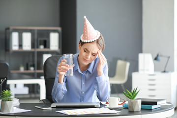 Young woman suffering from hangover in office