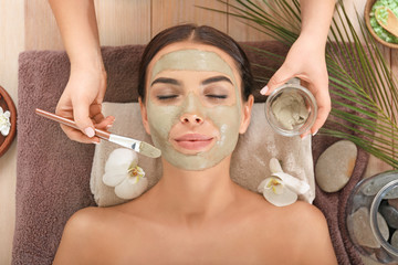 Cosmetologist applying mask onto face of young woman in spa salon