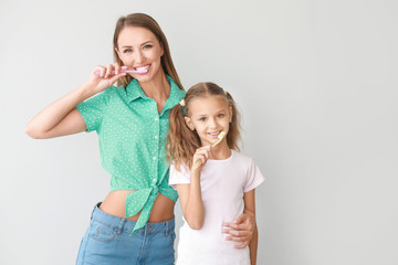 Fotomurales - Portrait of mother and her little daughter brushing teeth on light background