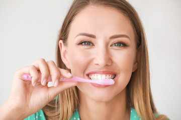 Fotomurales - Portrait of woman brushing teeth on light background