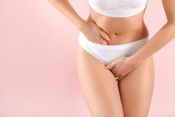 Young woman suffering from abdominal pain on color background. Gynecology concept