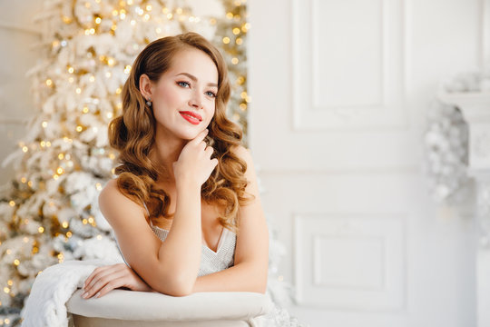Young beautiful woman smiling and happy looking camera, hair styling makeup, white silver color on background of Christmas tree and fireplace bokeh