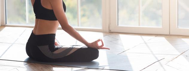 Cropped image of meditating woman sitting on yoga mat