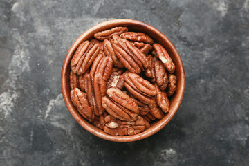 Bowl with tasty pecan nuts on dark background