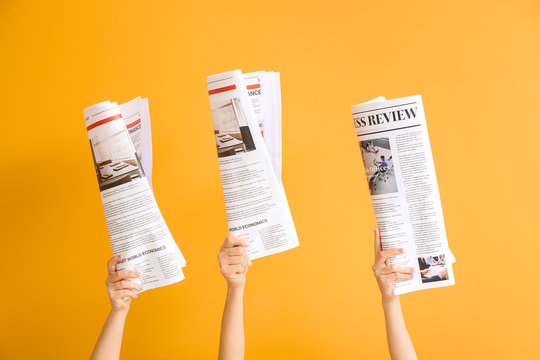 Female hands with newspapers on color background