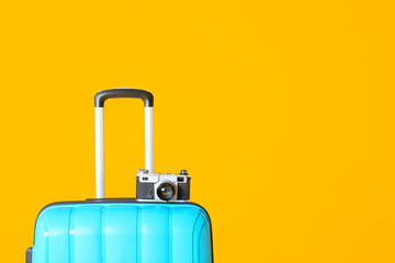 Packed suitcase and photo camera on color background. Travel concept Wall mural
