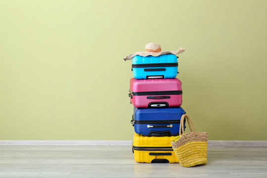 Packed suitcases near color wall. Travel concept