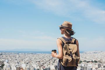 Young woman wearing hat looking at big city. Traveler girl enjoying vacation. Summer holidays, vacations, travel, tourism concept.