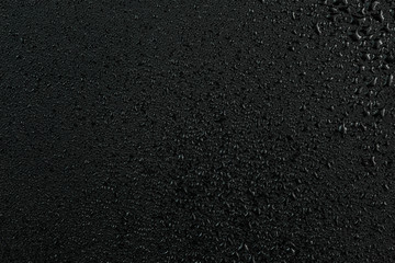 A dark abstract background of water drops on flat black rubber surface