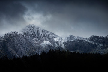 Aluminium Prints Dark grey Stunning dramatic landscape image of snowcapped Glyders mountain range in Snowdonia during Winter with menacing low clouds hanging at the peaks