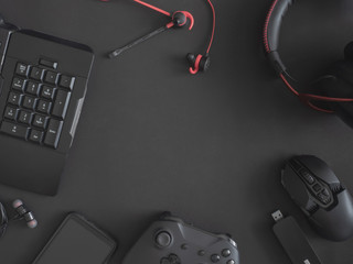 gamer work space concept, top view a gaming gear, mouse, keyboard, joystick, headset and in ear headphone on black table background.