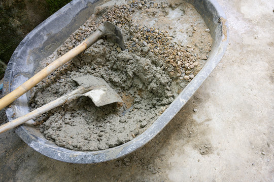 Mix cement sand and stones with hoe leak inside big bucket on floor background