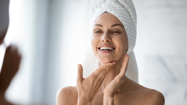 Happy lady look in bathroom mirror touching healthy face skin