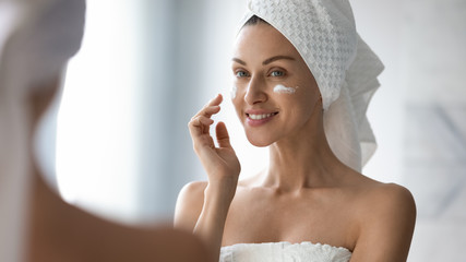 Smiling pretty lady put moisturizing facial cream look in mirror Wall mural
