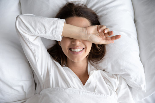 Smiling playful young attractive woman lying awake in comfortable bed