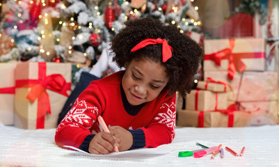 Little black girl lying on floor, writing letter to Santa