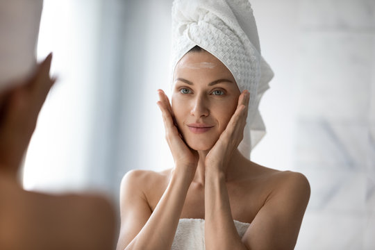 Beautiful young woman look in mirror massaging face applying cream