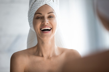 Happy woman towel on head laughing looking in mirror camera