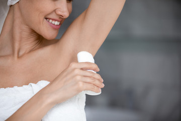 Printed roller blinds Spa Smiling woman wrapped with towel applying antiperspirant stick in armpit