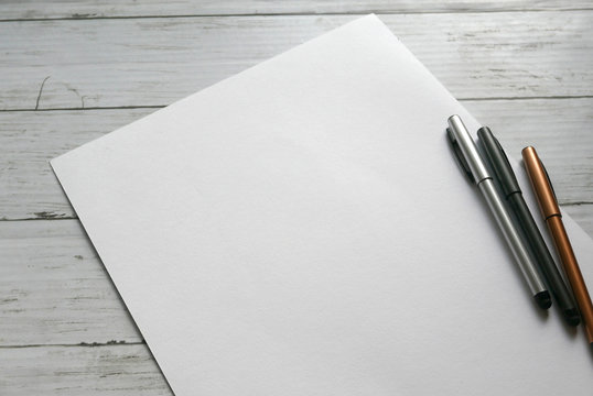 three pen on white paper background lay on white wooden background. Copy paste for text, logo and etc.