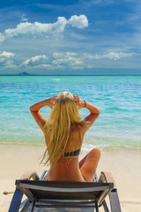 beautiful woman with blond hair relaxing on a tropical island with perfect beach.