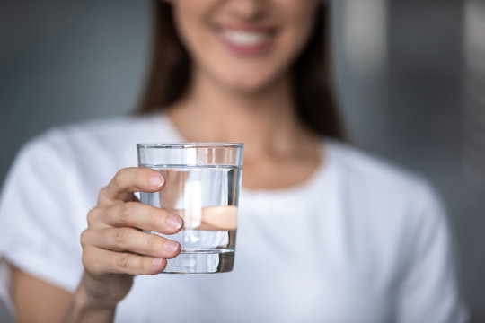 Smiling young lady holding glass of water, close up view